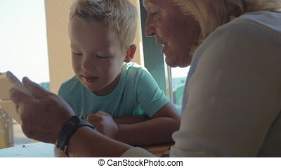 In city of Perea, Greece sits a grandmother with her grandson and teaches him how use tablet