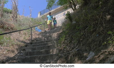 In city Perea, Greece in park down the stairs father with his son