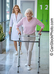 Woman with rolling-walker having rehabilitation procedures in clinic