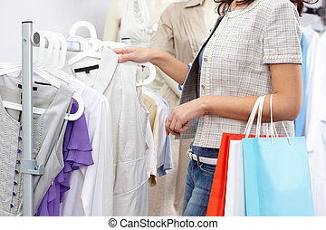 In clothing department - Close-up of female choosing new...