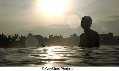 In coast - Silhouette of professional surfer on surf board...