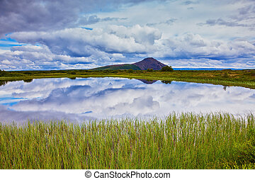 In cold lake reflects cloudy sky