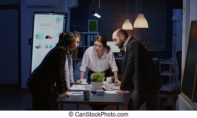 In corporate meeting room diverse multi ethnic group of businesspeople lean on conference table brainstorming project ideas late at night. Teamwork overworking at management presentation