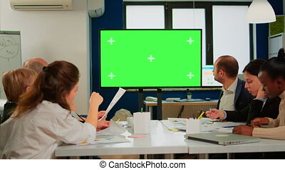 In corporate office meeting room stands green mock-up screen TV or interactive digital whiteboard in horizontal mode. Multiethnical businesspeople working, brainstorming in professional start up