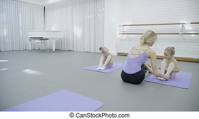 In dance studio coach corrects position of little girls sitting.