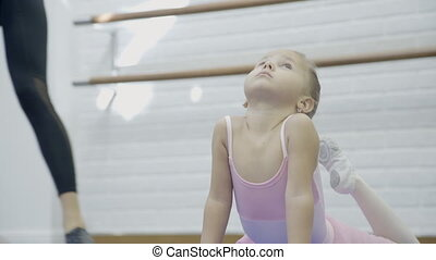 in dance studio girl stretches toes feet in of head with...