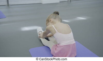 In dance studio little girl is sitting and doing stretching...