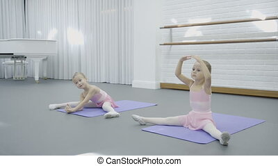 In dance studio two girls sit on mats and learn how to do...