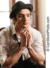 In deep thought. Handsome young stylish man sitting on the chair with his hands on chin