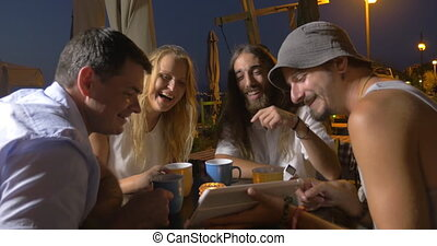 In evening in city of Perea, Greece at the table in cafe sits a young company
