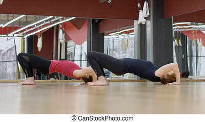 In fitness club two women perform a gymnastic bridge...