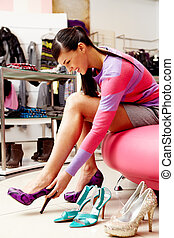 In footwear department - Image of lady trying on several...