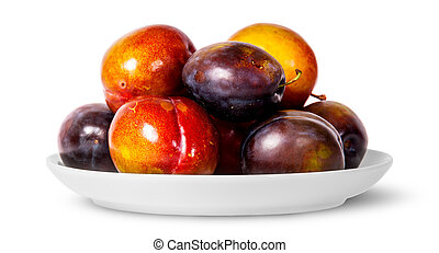 In front mix of red and violet plums on white plate