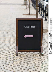 In front of the coffee shop with black board stand