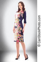 charming female model in a stylish designer dress