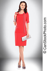 elegant woman model in red dress and with stylish handbag