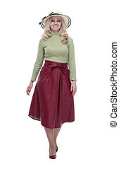 smiling woman in a summer hat striding forward