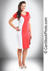 in full growth. smiling woman model in stylish red and white dress