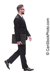 in full growth. successful businessman with laptop stepping forward.