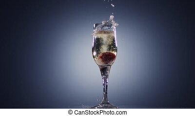 In glass with champagne wine falling fresh strawberry, slow...