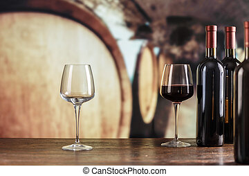in glasses of red wine on a background of large barrels