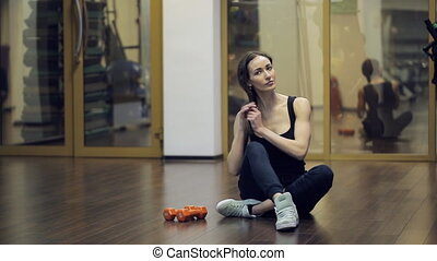 In gym after exercise with dumbbells woman corrects her hair.