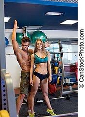 Bodybuilder posing and girl laughing at camera