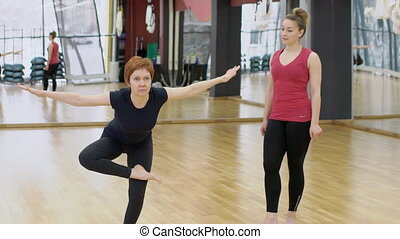 In gym coach shows the woman an exercise in the form of a...