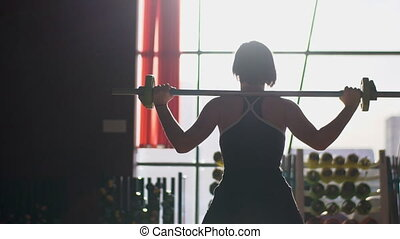 In gym on background of light woman lifts bar on her shoulders.