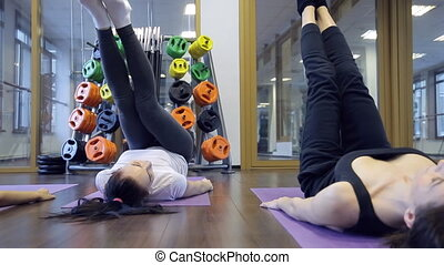 In gym three young women are lifting legs lying on a purple...