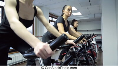 In gym three young women stand actively going on an exercise bike.