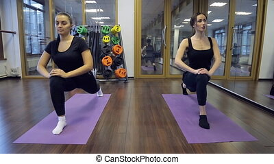 In gym two young women sitting down on a forward split on mats.