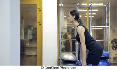 In gym young athlete raises body holding dumbbells in hands....
