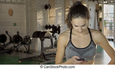 In gym young woman in a sports top looks at phone.