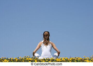 In harmony with nature. Young woman in white clothes sitting in a flowering dandelion field.