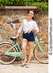 In her own style. Full length of beautiful young smiling woman standing near her vintage bicycle