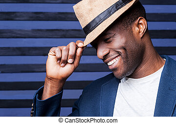 In his own unique style. Handsome young African man adjusting his hat and smiling while standing against striped background