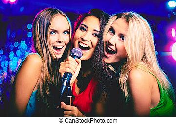 In karaoke bar - Portrait of happy girls singing in ...