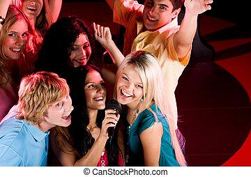 In karaoke bar - Portrait of happy people singing in ...