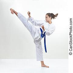 In karategi, a sportswoman strikes a kick