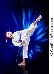 In karategi athlete beats kicking against the blue glow