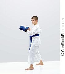 In karategi karateka boy is standing in the rack of karate