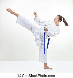 In karategi the sportswoman beats a high kick leg