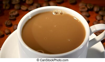 In latte added a lump of sugar and stir a small spoon, white cup and saucer into which is poured drink, on brown wooden table are scattered coffee beans, closeup