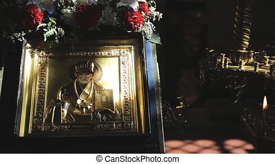 In light beam there is an icon with image of holy man with flowers. St. Nicholas.