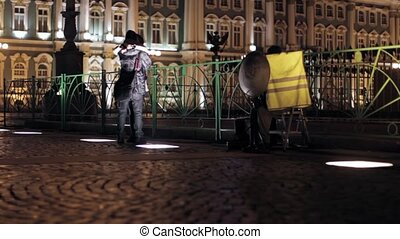 In love couple hugs in night street. Hermitage in Saint Petersburg on background