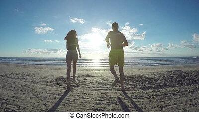 In love couple running on a beach towards the sea