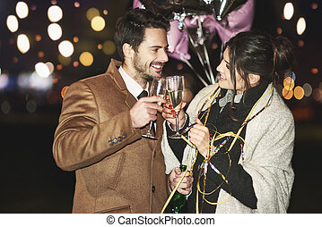 In love couple toasting outdoors