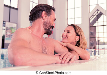 Happy positive couple swimming in the pool together