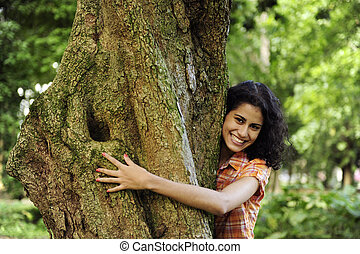 In love with nature: woman hugging a tree in the forest
